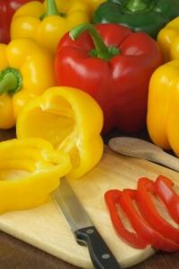 Foto: Gelbe und rote Paprika auf einem Schneidebrett mit Messer