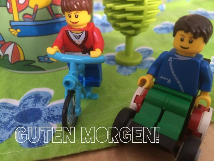 Foto: LEGO Wheelchair-Figur zusammen mit einer LEGO-Figur auf dem Fahrrad