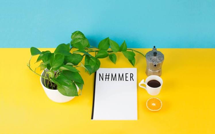 """Foto: Pflanze, weißes Blatt mit Aufdruck """"N#MMER"""", Kanne Kaffee, gefüllte Kaffeetasse und eine Scheibe Orange liegen auf blaugelben Untergrund"""