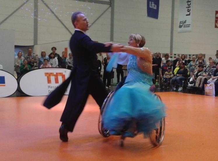 Foto: Frau im Rollstuhl tanzt mit ihrem Mann