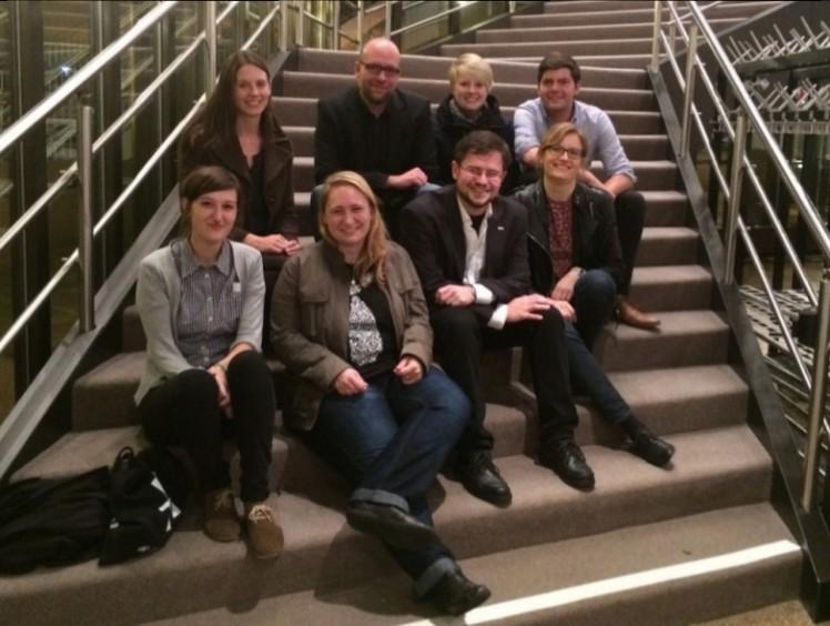Foto: Mehrere Menschen sitzen auf einer Treppe für ein Gruppenfoto