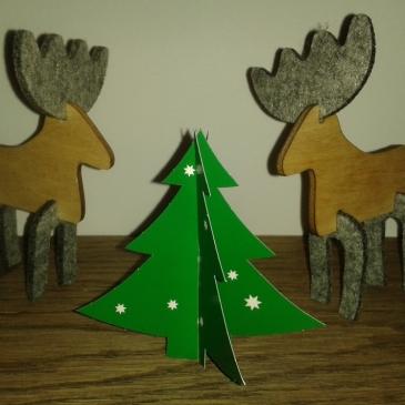 Foto: Zwei Rentiere aus Holz und Filz stehen neben einem Tannenbaum aus Papier