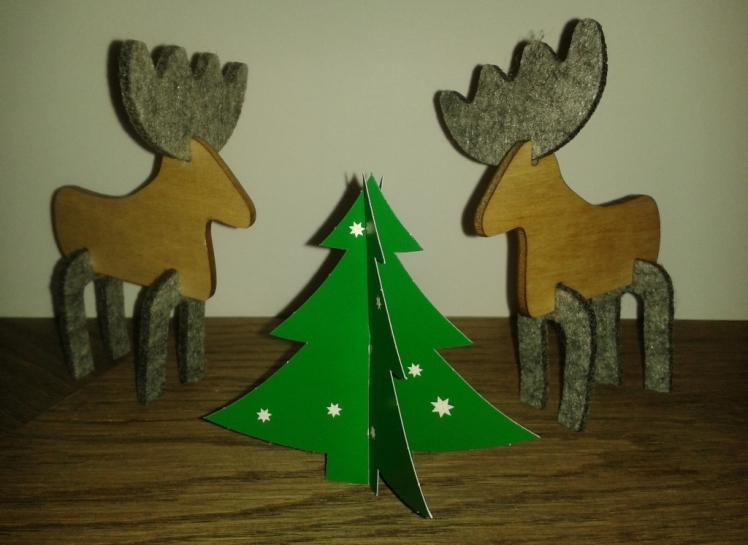 Foto: Zwei Rentiere aus Holz und Filz stehen um einen Papiertannenbaum