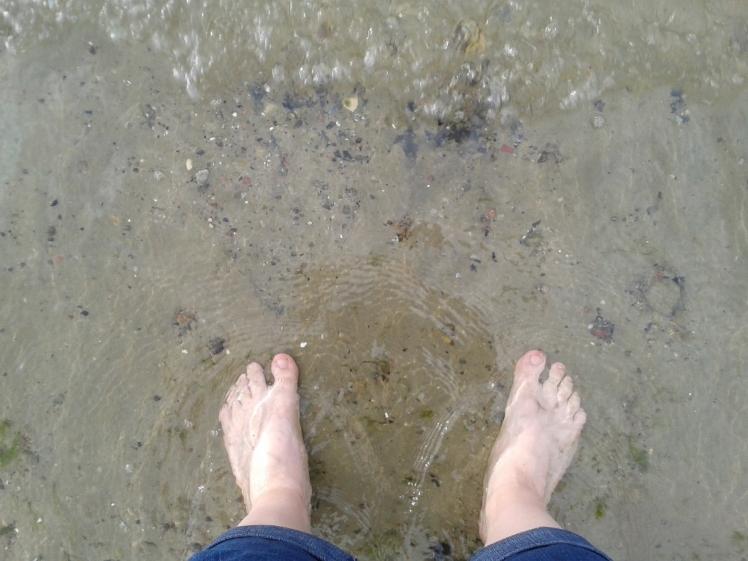 Foto: Mit den Füßen im Wasser stehend