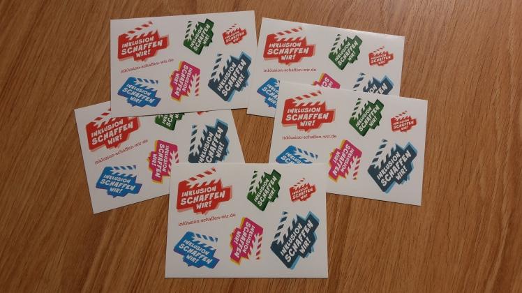 """Foto: 5 Postkarten mit bunten Logo-Aufklebern von """"Inklusion schaffen wir"""""""
