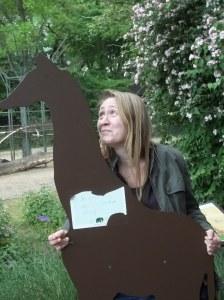 Foto: Ich hinter einer hölzernen Babygiraffe, man sieht nur meinen Oberkörper