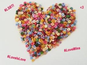 Foto: Bunte Knöpfe zu einem Herz gelegt, mit den Hashtags #LSBTI, #LoveIsLove und #LoveWins