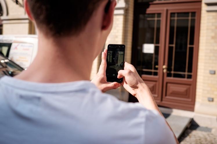 Foto: Mann macht mit dem Smartphone ein Foto von einer Rampe an einem Eingang