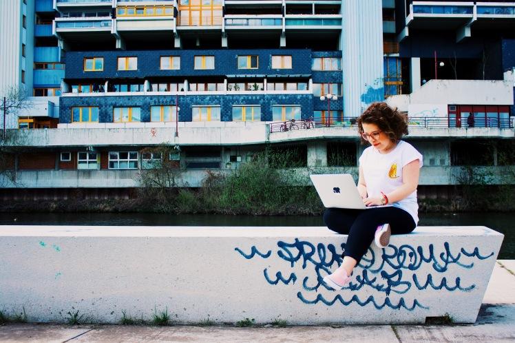 Foto: Ninia LaGrande sitzt auf einer Mauer und tippt auf dem Laptop