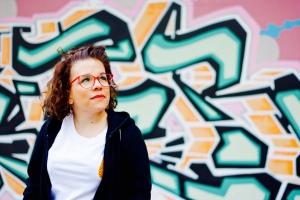 Foto: Ninia LaGrande vor einer Wand mit Graffiti