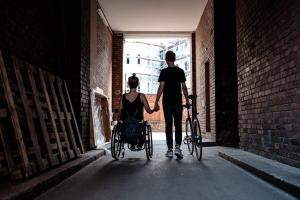 Foto: Eine Rollstuhlfahrerin wird von hinten gezeigt, wie sie sich Händchen haltend mit ihrem Freund in einer Gasse befindet. Der Freund ist kein Rollstuhlfahrer und schiebt stattdessen mit der freien Hand ein Fahhrad