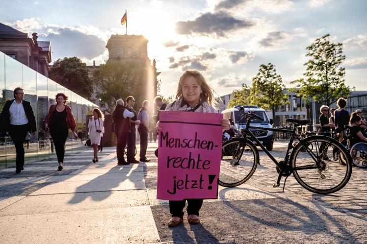Foto: Kleinwüchsige blonde Frau lächelt in die Kamera und hält ein pinkes Schild in der Hand, auf dem steht: Menschenrechte jetzt!