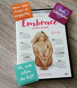"""Foto: Die DVD-Hülle der Doku EMBRACE ist zu sehen. Darauf liegen drei farbige Sticker mit jeweils dem Aufdruck: """"Wow, dein Körper ist einzigartig!"""", """"Yeah, Selbstliebe!"""" und """"Oh, wie schön du bist!"""""""