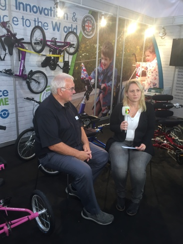 Foto: Nadine sitzt auf der REHACARE 2017 mit einem Mikrofon in der Hand neben ihrem Interviewpartner Bob