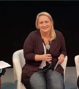 Foto: Nadine kurz vor der Podiumsdiskussion auf der REHACARE 2018. Sie sitzt auf einem Stuhl und hält ein Mikrofon in der Hand.